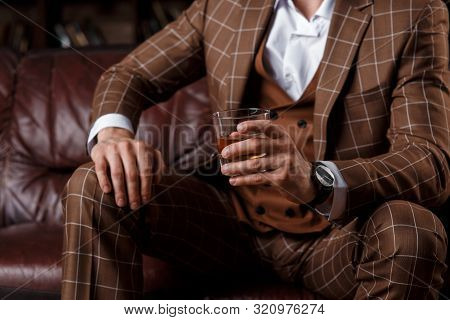 Young Successful Man In A Brown Kosmtyum Drinks Whiskey. Bearded Businessman Sitting In A Library On