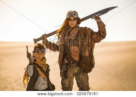Post-apocalyptic Woman And Boy With Weapons Outdoors. Desert And Dead Wasteland On The Background. A