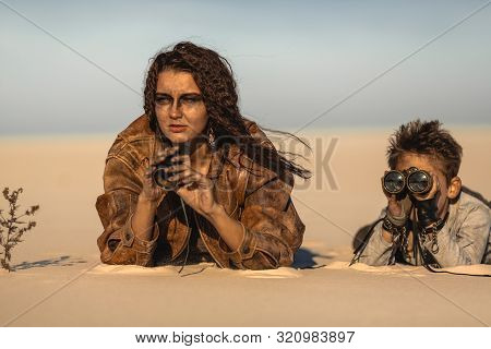 Post Apocalyptic Woman And Boy With Binoculars Outdoors. Desert And Dead Wasteland On The Background