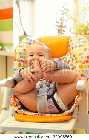 Smiling Baby Boy Sitting In The Highchair