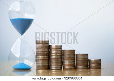 Hourglass Blue Sand And Stack Of Coins. Business Investment Growth Concept. Money Saving And Investm