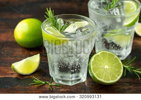 Gin And Tonic Alcohol Drink With Lime, Rosemary And Ice On Wooden Table
