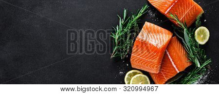 Salmon. Fresh Raw Salmon Fish Fillet With Cooking Ingredients, Herbs And Lemon On Black Background,