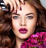 Beautiful  woman with purple make-up of lips and fingernails. Closeup woman's portrait with flowers. Young caucasian gorgeous adult girl with long brown curly hair. Model. Vivid make-up.  poster
