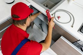 Plumbing Services - Plumber Working In Domestic Kitchen, Repairing Sink Pipes