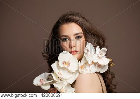 Young Perfect Model Woman With Long Perfect Curly Hair And White Flowers On Brown Background