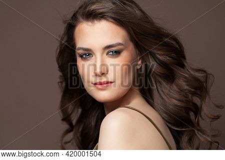 Portrait Of Pretty Smiling Woman Brunette With Clear Skin And Healthy Wavy Hair On Brown Background.