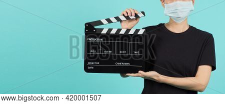 Asian Woman Wear Face Mask And Hand's Hold Black Clapper Board Or Movie Slate Use In Video Productio