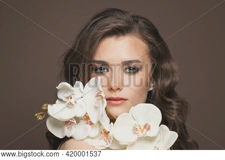 Nice Woman With Healthy Clear Skin And White Orchid Flowers Portrait. Facial Treatment And Skin Care