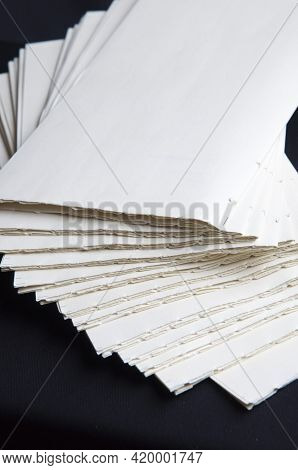 The Process Of Book Binding; Pile Of Raw Paper Folders. Black Background