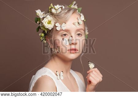 Perfect Young Woman With White Spring Flowers And Butterfly On Brown Background