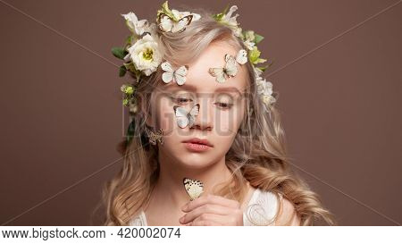 Portrait Of Attractive Blonde Woman With Healthy Wavy Hair, White Spring Flowers And Butterfly On Br