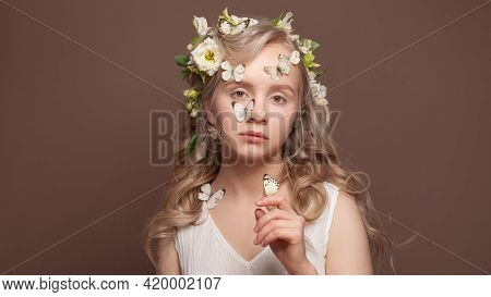 Nice Young Woman With Healthy Hair, White Spring Flowers And  Butterfly On Brown Background