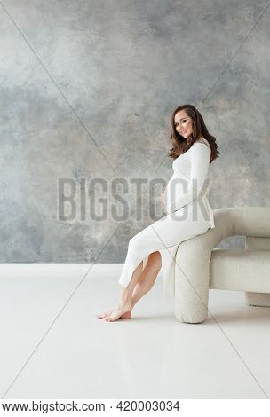 Pregnant Woman In White Dress Sitting On Armchair On Gray Banner Background