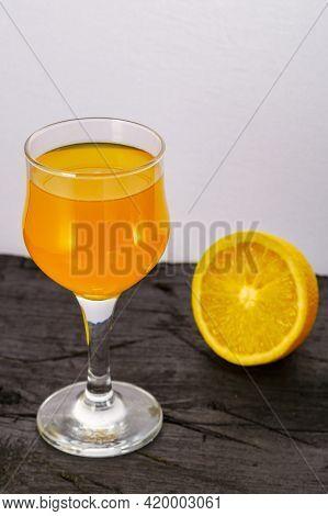 Orange Juice In A Glass Near Oranges On A Black Background. Vertical Photo