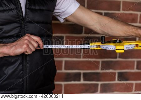 Man's Hands Holding Length Centimetre Ruler For Building Use Against Red Brick Wall. Copy Space. Foc
