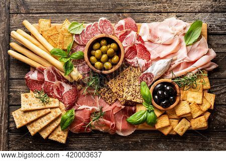Appetizers With Differents Antipasti, Charcuterie, Snacks And Red Wine. Sausage, Ham, Tapas, Olives