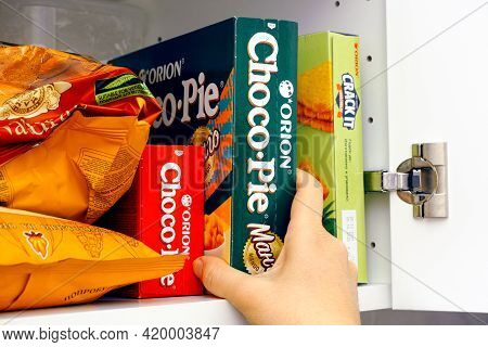 Tambov, Russian Federation - January 25, 2021 Woman Taking Orion Choco-pie Mango Box Out Of A Cupboa