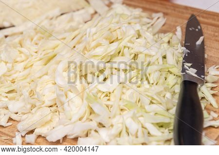 Close-up Of Chopped White Cabbage On A Wooden Board On The Kitchen Table. Home Cooking Concept, Vege