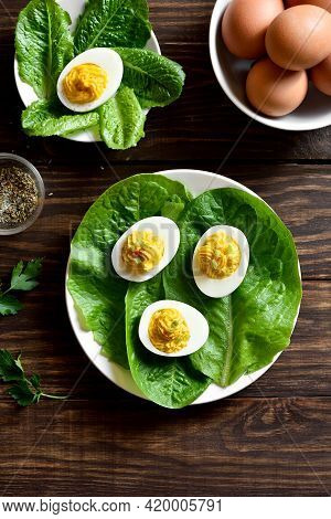 Deviled Eggs With Paprika, Mustard And Mayonnaise On Plate Over Wooden Background. Top View, Flat La