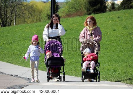 Moscow, Russia - May 2021: Two Young Woman Walking With Prams And Little Girl In Park. Family Leisur