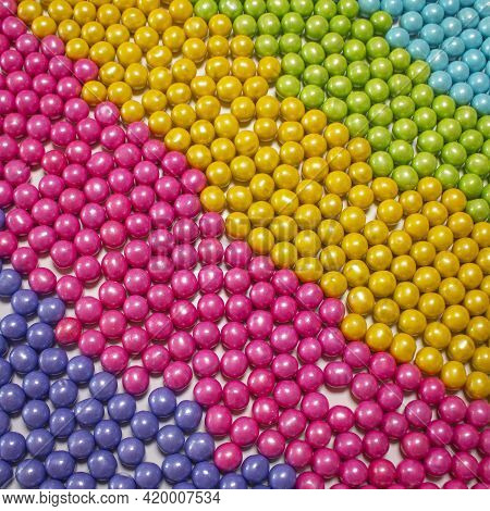 Diagonal Slant Display Of Round Candy Coated Chocolate Sweet Treats In Purple Pink Yellow Green And