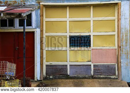 Old Abandoned Warehouse Building Structure Garage Door With Yellow Pink Red And Blue Highlight Color