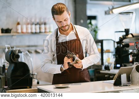 Portrait Of Handsome Barista Standing In Behind The Counter Bar And Smiling While Wiping Ceramic Cup