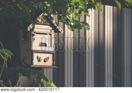 Sunlight And Shadow On Surface Of The Old Wooden Mailbox With Green Branch On Artificial Wood Gate I