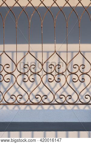 Sunlight And Shadow On Abstract Pattern Surface Of The Old Grunge Wrought Iron Fence On Terrace In V