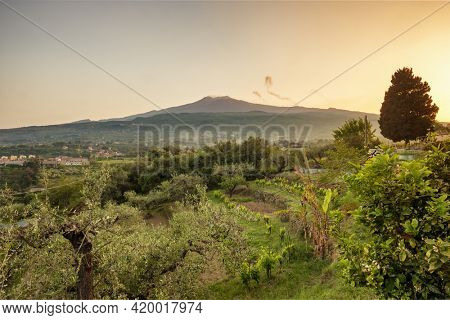 Sicilian rural landscape with Etna volcano eruption at sunset in Sicily, Italy