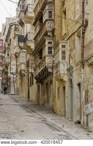 Valletta. Malta - February 20, 2010. Narrow Street Of Capital Of Malta. Stone Buildings With Old Fas