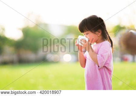 Selective Focus. Cute 4 Year Old Girl Drinking Some Water From A Plastic Cup. Child Is Thirsty. Chil