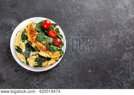 Frittata Made Of Eggs, Cheese And Spinach Salad. Frittata - Italian Omelet On A White Plate On A Gra