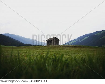 Alpine Mountain Panorama Of Idyllic Remote Wooden Shed Cabin In Green Grass Field Meadow Of Dolomite