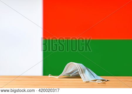 A Medical Mask Lies On The Table Against The Background Of The Flag Of Madagascar. The Concept Of A