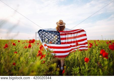 A Girl Runs Across A Poppy Field With An American Flag. Young Woman With Flag On Independence Day. G