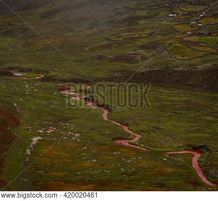 Red Coloured River Stream From Sandstone Mineral Sediment Erosion In Green Grass Meadow Valley Lands