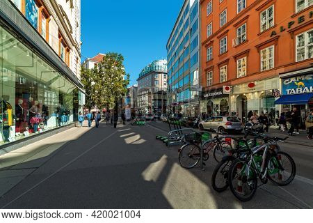 VIENNA, AUSTRIA - SEPTEMBER 27, 2018: Bicycles on pedestrian street and people walking among houses and shop windows in historic part of Vienna - capital city, famous and popular tourist destination.