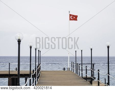 Deserted Pontoon With Orange Life Buoy And National Flag Of Turkey. Empty Hotels And Guesthouses Bec