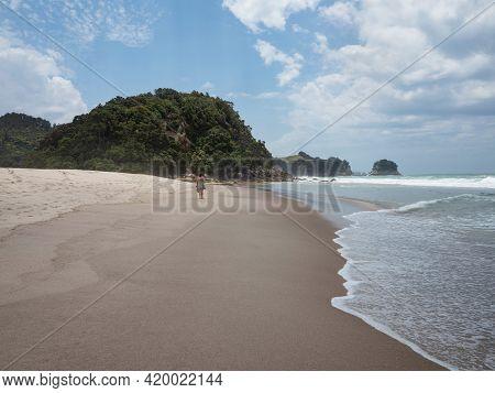 Female Tourist Walking Along Pacific Ocean White Sand Beach Whiritoa In Hauraki Coromandel Peninsula
