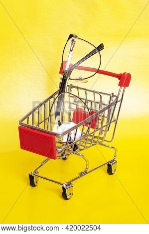 Eyeglasses In A Shopping Cart On Yellow Background Close Up
