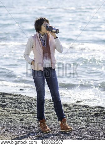 Smiling Woman Walking On Seaside With Metal Travel Mug. Vacation On Ocean Coast. Turquoise Water Beh