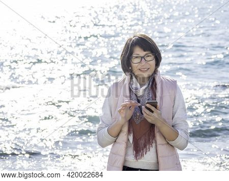 Smiling Woman Texting Somebody On Smartphone. Active Recreation On Seaside. Vacation On Ocean Coast.