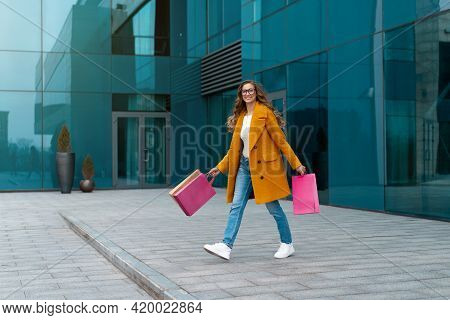 Business Woman With Shopping Bags Dressed Yellow Coat Walking Outdoors Corporative Building Backgrou