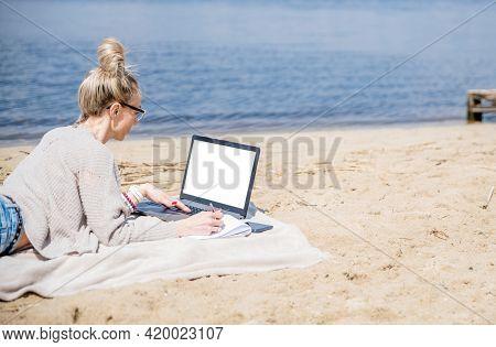Woman Working At A Lake, Using Laptop. Freelance Work.