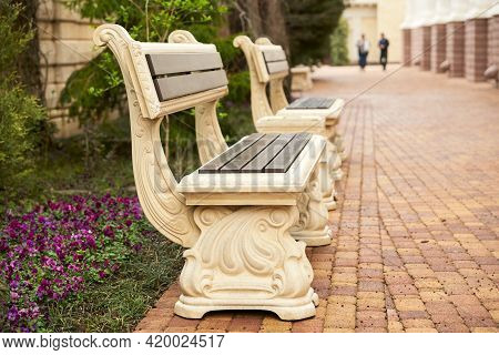 Two Vintage Benches On An Alley In The Park. At The End Of The Alley, You Can See The Figures Of Rar