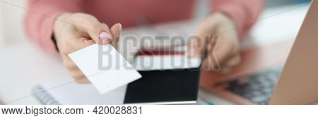 Female Hand Holds Out A Business Card At Workplace