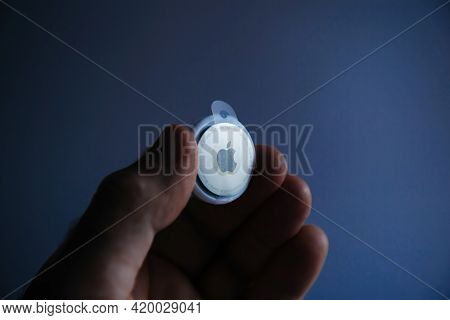 Paris, France - May 2, 2021: Man Holding New Airtag Blue Tech Background - Small Device Helps People