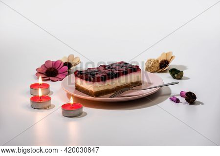 Slice Of Cheesecake With Raspberry And Currant Sauce In A Pink Plate, With Romantic Candles Set, Clo